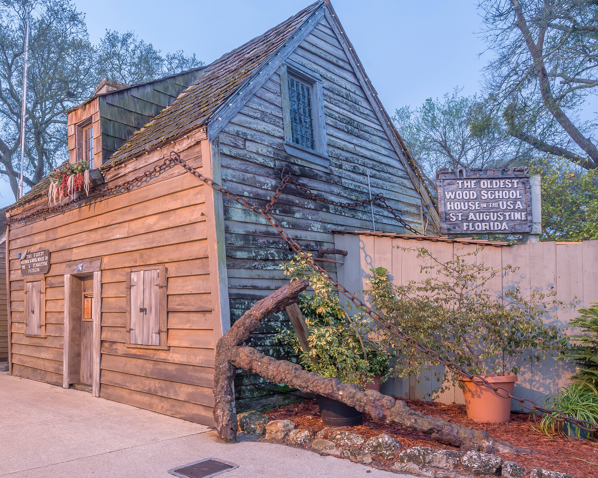 """The oldest wood school house in the USA"" sign hangs outside a tiny ancient building, representing education practices of the past that still present barriers today."
