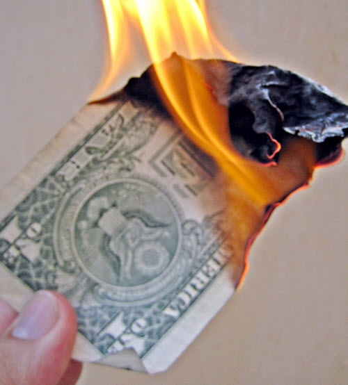 A one dollar bill deliberately set on fire.