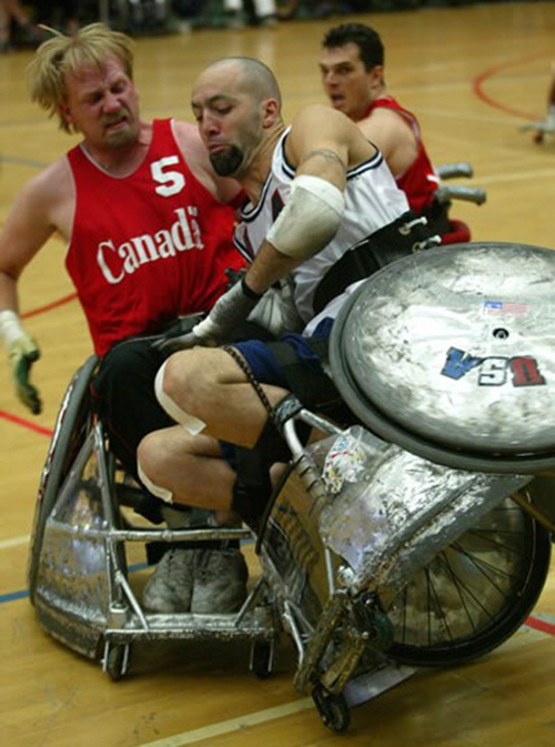 Wheelchair rugby athletes in the heat of an intense battle. One athlete is tilted agaisnt the other, with a wheel of his much dented chair about 3 feet in the air.