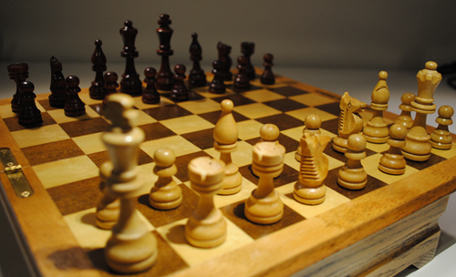 A chessboard with one side regimented in the starting position. The other side's pieces are all lined up randomly, as if they don't know where they should start.