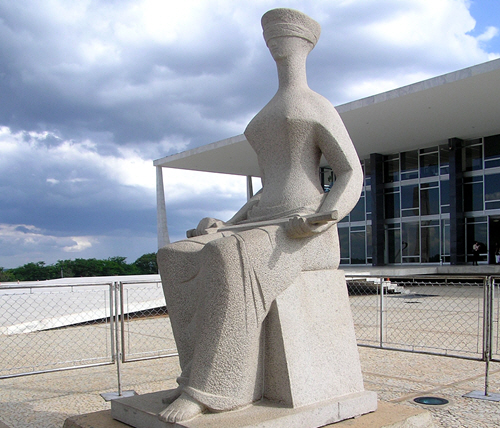 A modern statue of a seated Lady Justice with the blindfold as a prominent feature