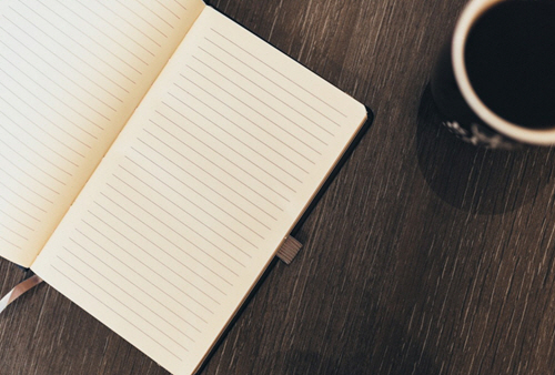 A blank notebook sits on the desk. A cup of coffee might inspire writing.