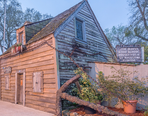 """The oldest wood school house in the USA"" sign hangs outside a tiny ancient building. Education practices of the past present barriers today."