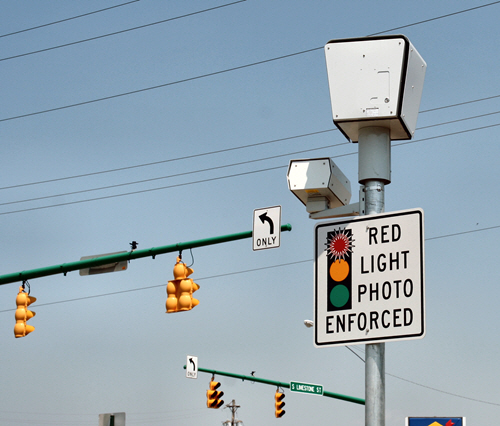 A traffic enforcement camera high up on a pole, with a sign warning that Red Light violations are photo enforced.